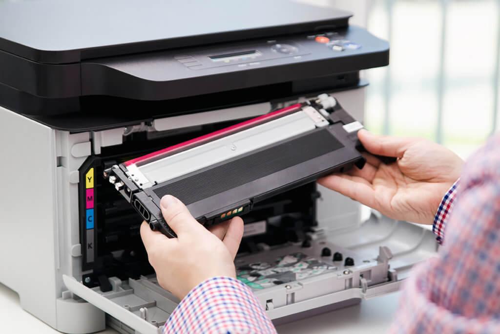 Mann ersetzt Toner in einem Multifunktionsdrucker.