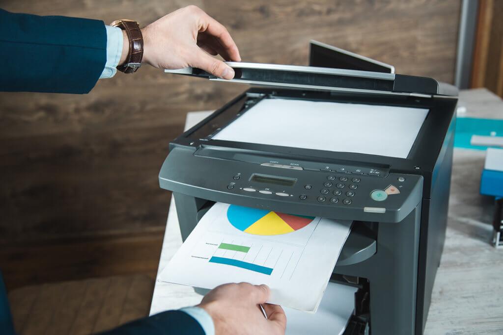 Mann zieht bedrucktes Papier aus einem Multifunktionsdrucker und oeffnet die Abdeckung der Scanauflage.