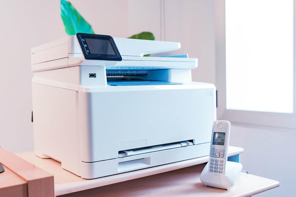 Ein weisser Multifunktionsdrucker steht in einem hellen Buero.