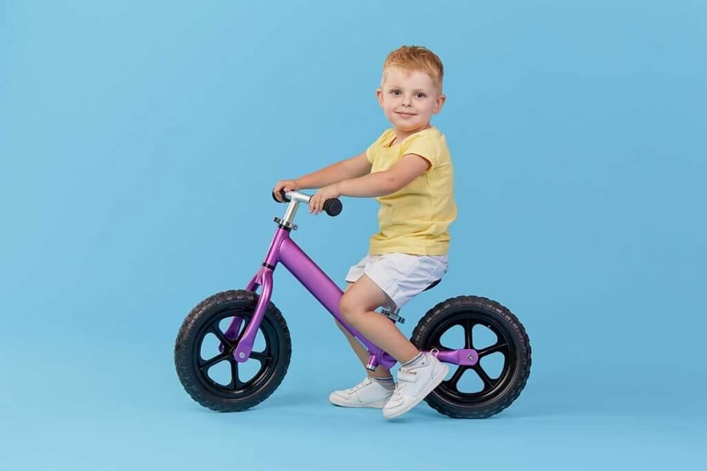 Junge sitzt auf Lila Laufrad mit blauem Hintergrund