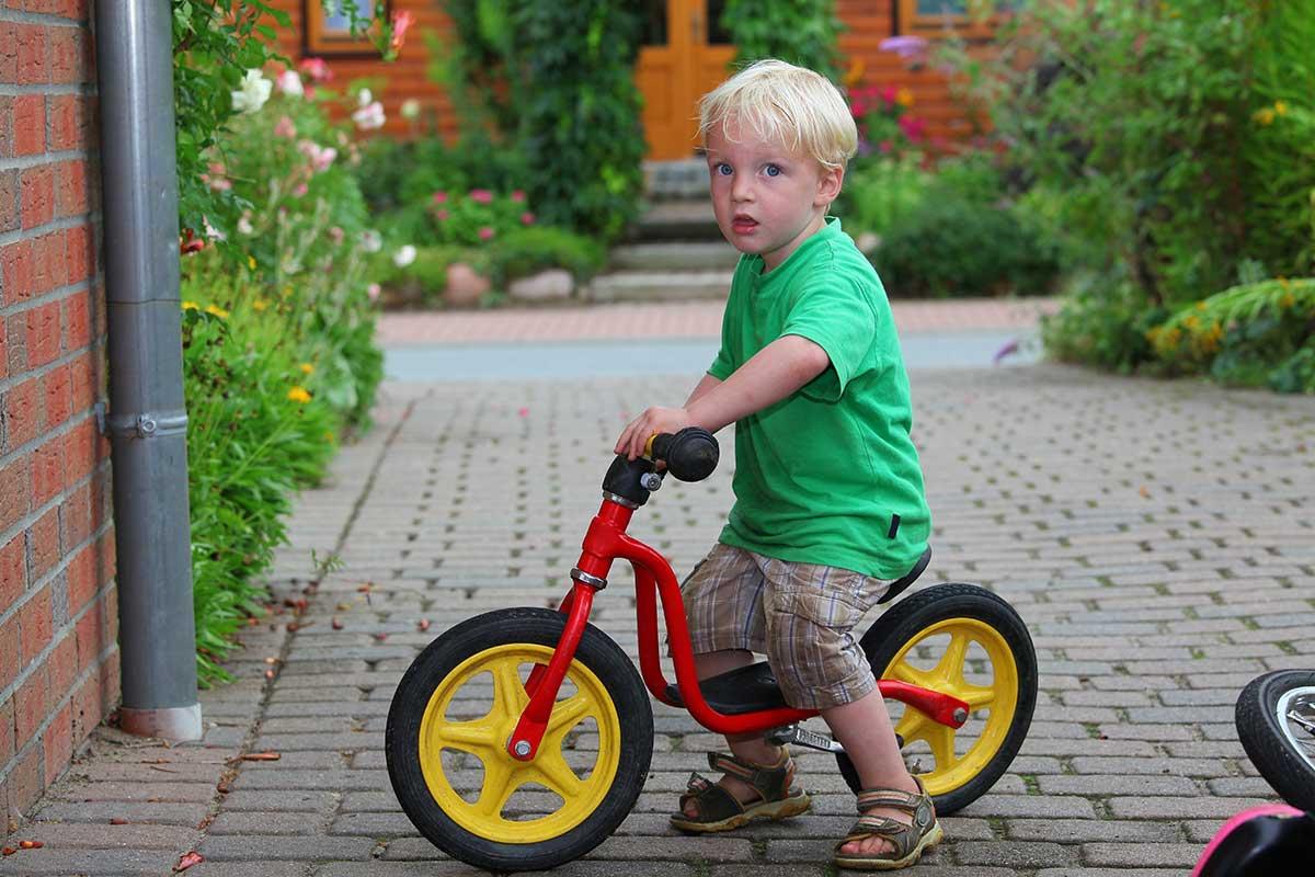 Junge sitzt aufrecht auf Laufrad