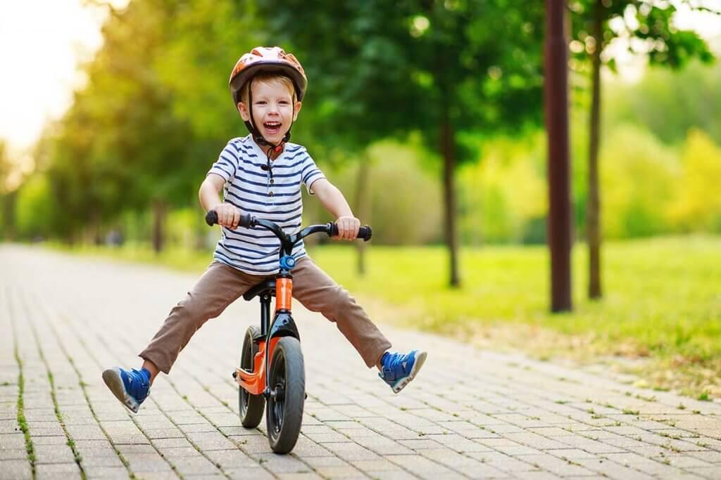 Kleiner Junge faehrt durch den Park