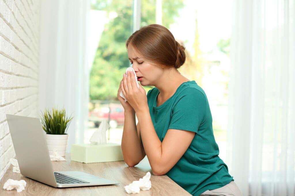 Frau sitzt am Tisch vor einem Laptop und putzt sich die Nase