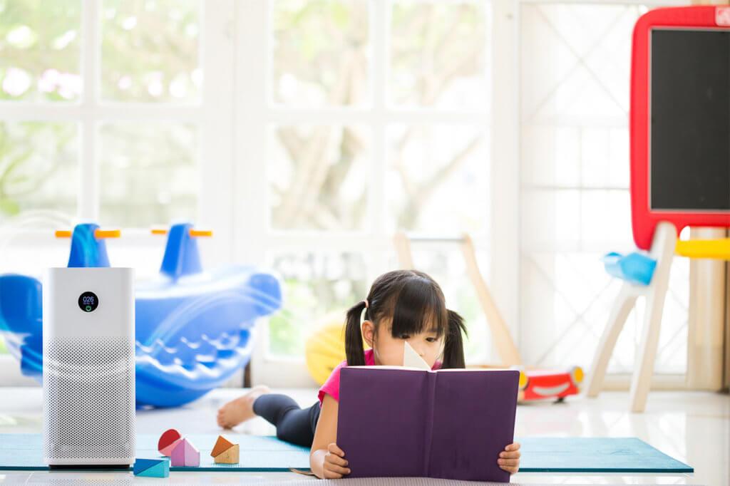 Kleines Kind liegt auf dem Boden und liest in einem Buch - daneben steht ein Luftreiniger