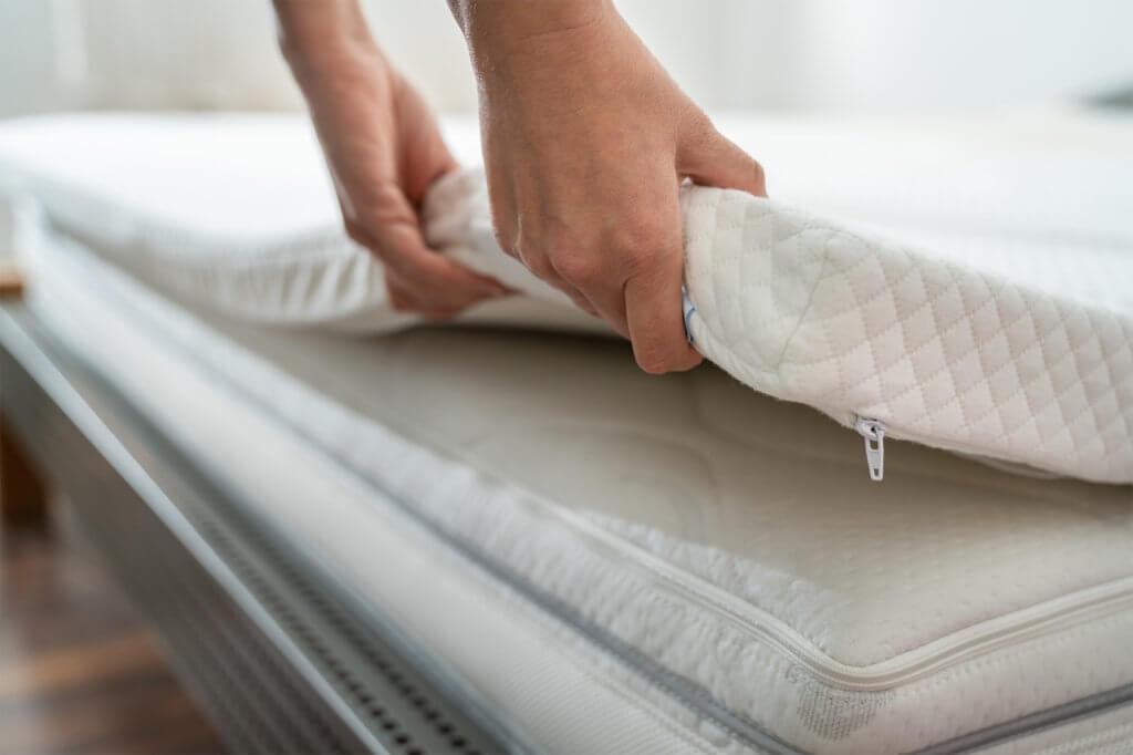 Person platziert einen Matratzen-Topper