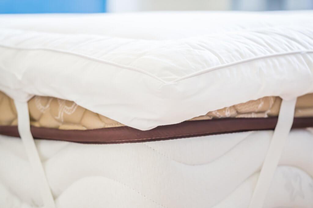 Seitenansicht auf Matratze und Matraten-Topper