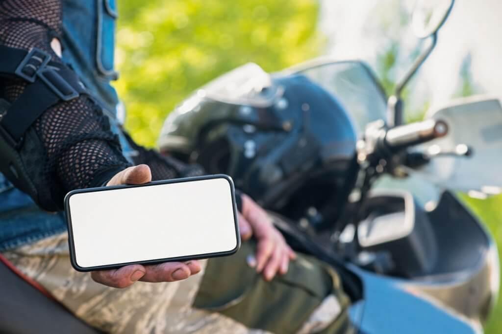 person auf motorrad zeigt smartphone