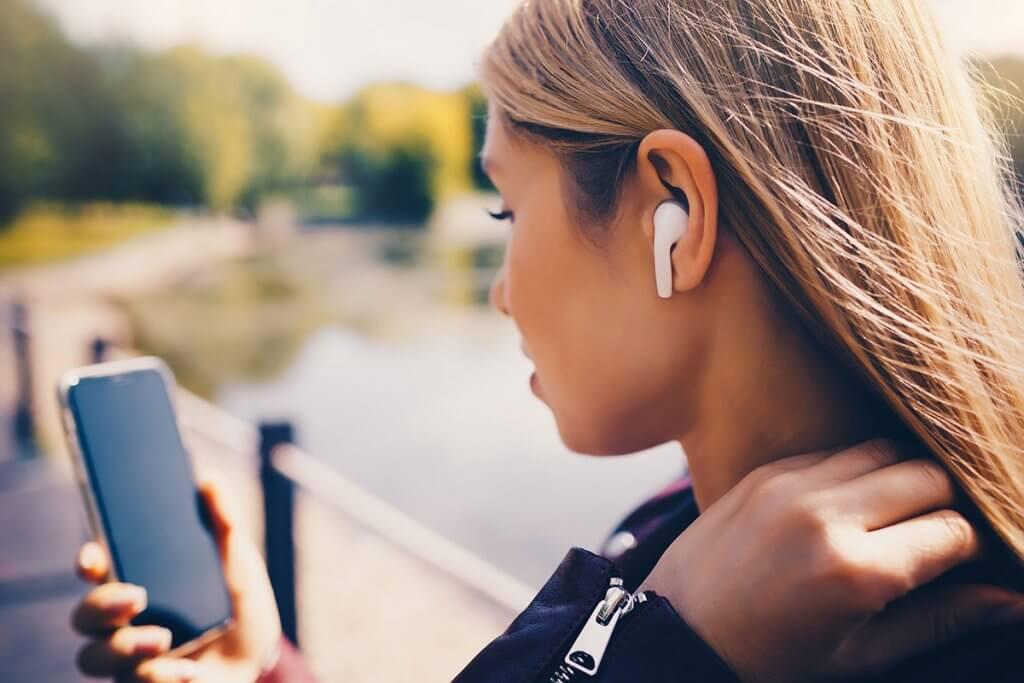 frau in motorradkleidung traegt ear pods