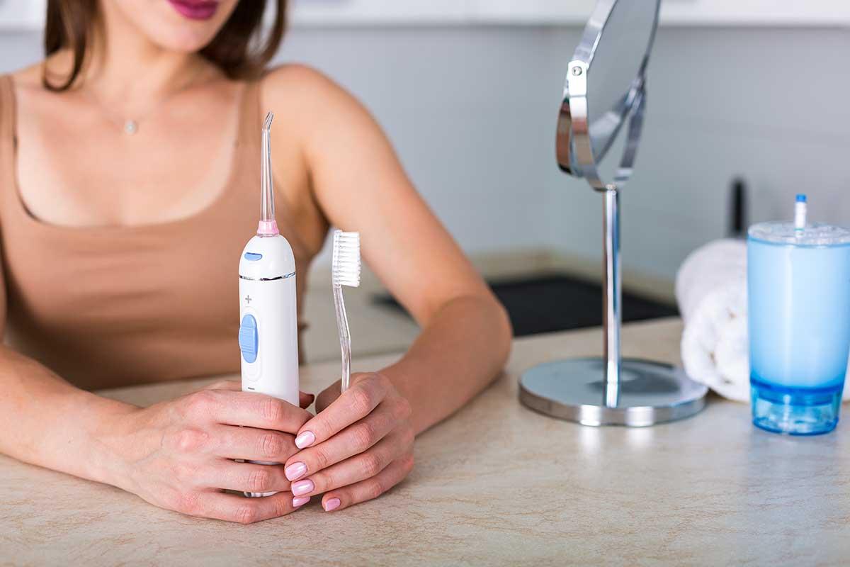 Frau haelt Zahnbuerste und Munddusche in den Haenden