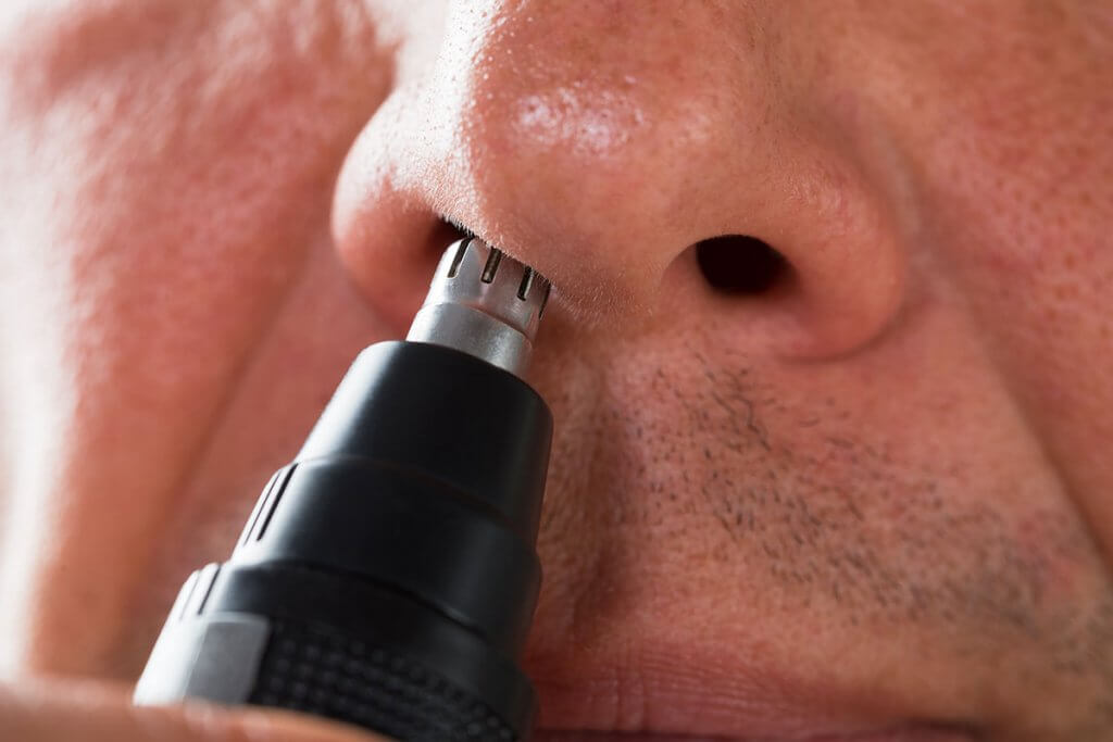 close-up von einem Mann, der einen Nasenhaartrimmer nutzt
