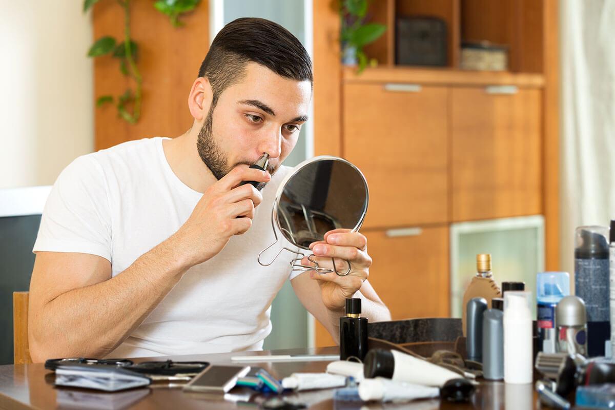 Mann trimmt sich die Nasenhaare am Spiegel
