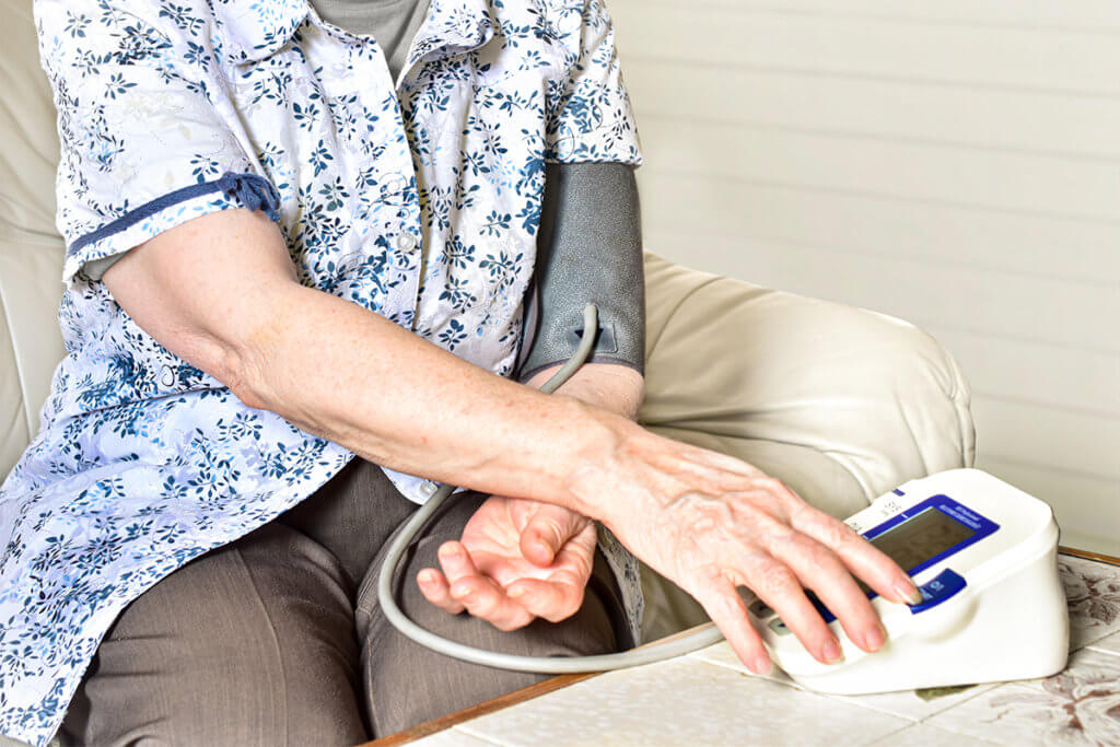 Torso einer aelteren Dame, die ihren Blutdruck misst