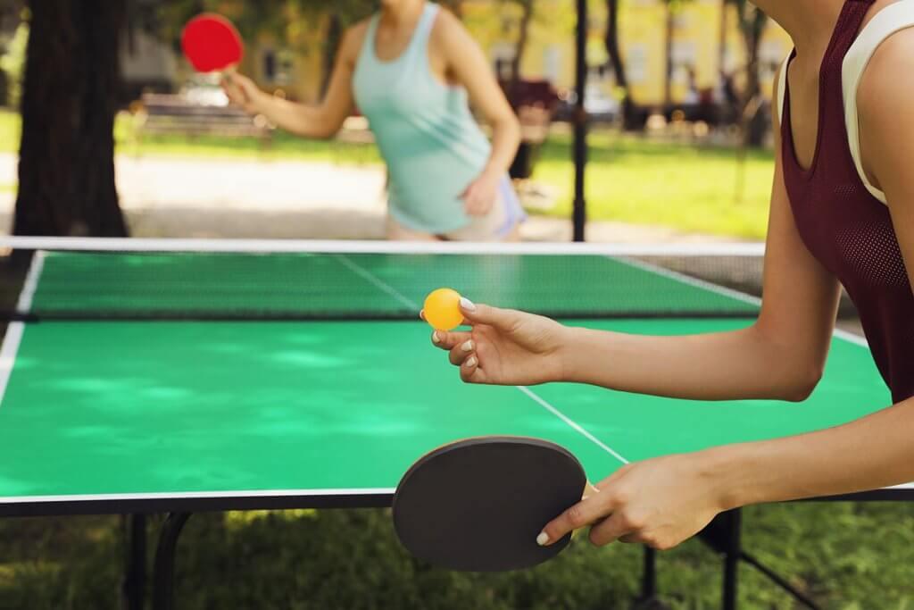 zwei Frauen spielen Tischtennis im Freien