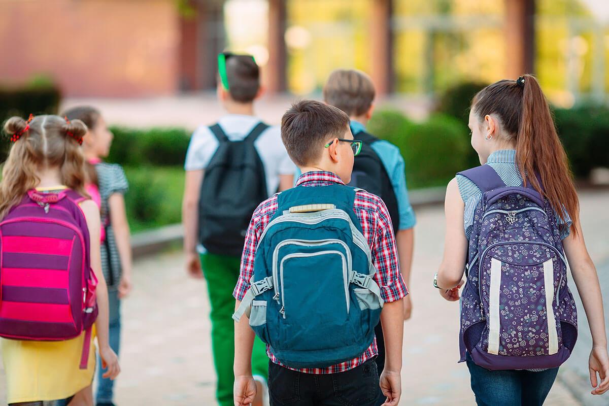 Gruppe von Schulkindern mit Rucksaecken auf dem Weg zur Schule