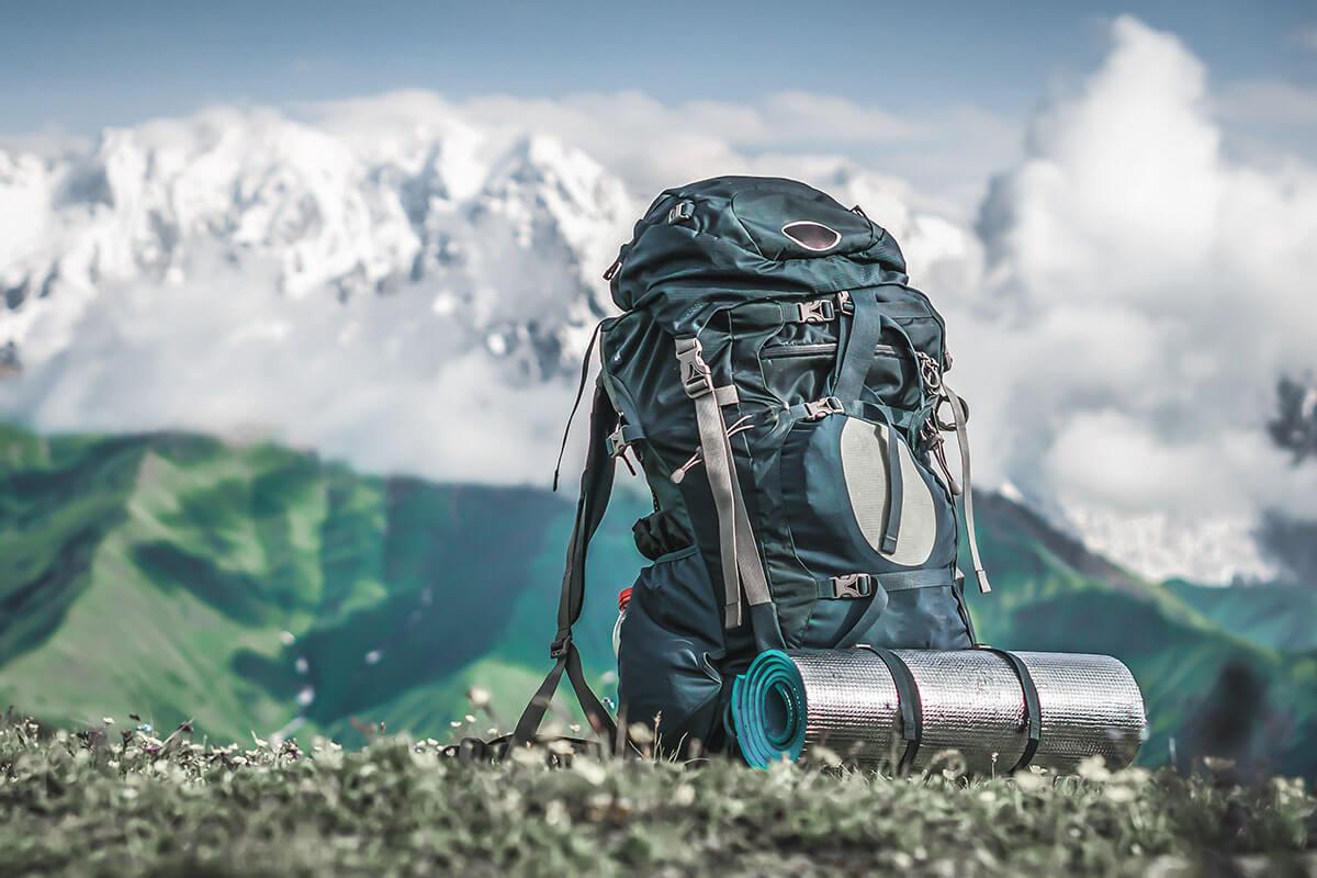 Gepackter Wanderrucksack samt Isomatte in Berglandschaft