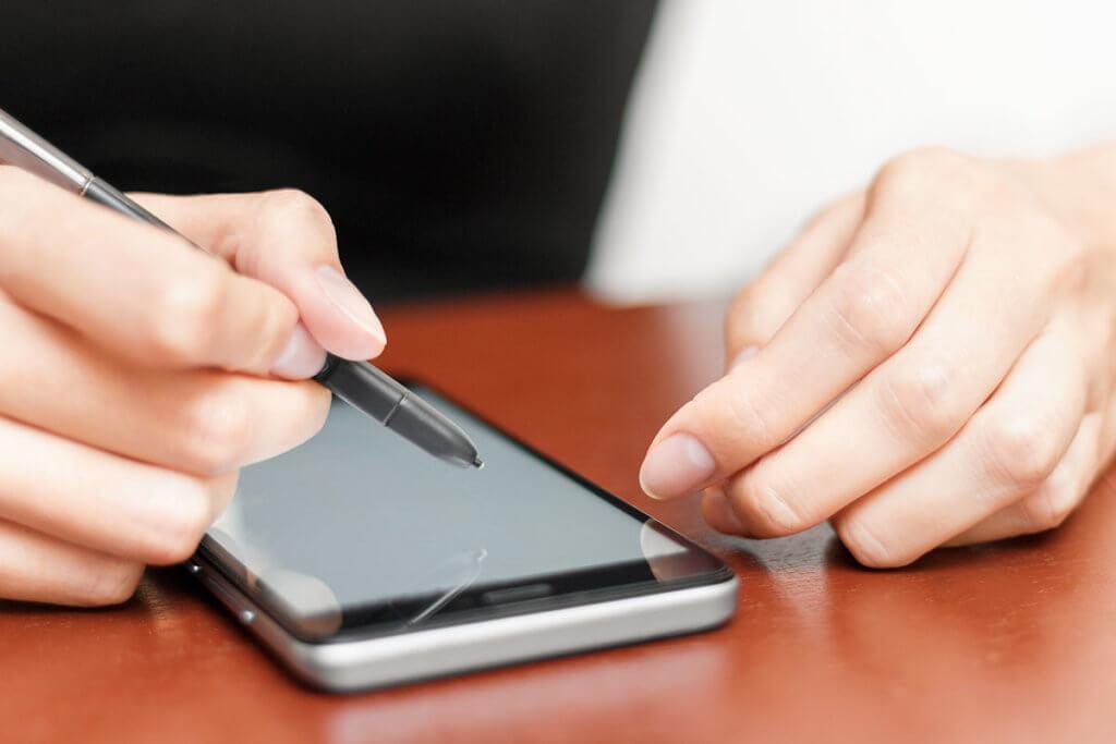 Frau bedient Smartphone mit Stift
