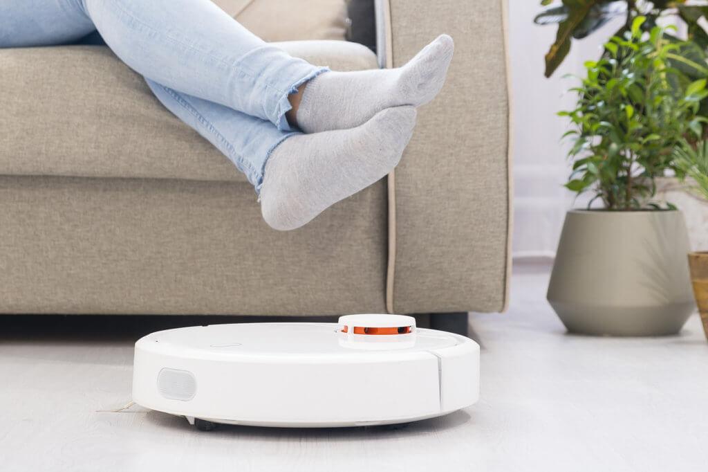 Frau sitzt auf Sofa und ein Saug-Wisch-Roboter faehrt unter den Fuessen durch
