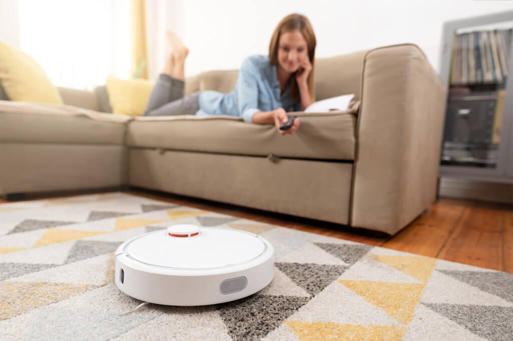 Frau liegt auf Sofa und steuer Saug-Wisch-Roboter