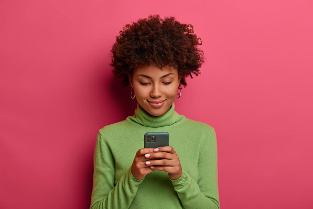 Frau mit Smartphone vor pinker Wand