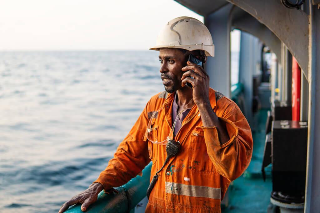 Mann auf Schiff nutzt Smartphone