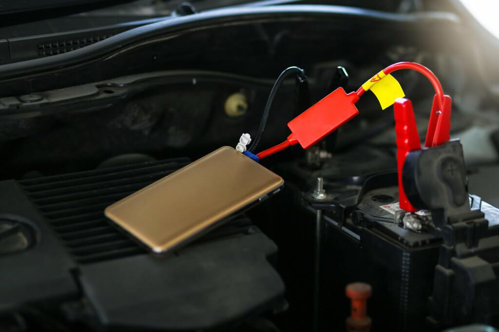 Kleine Starthilfegeraet haengt an Autobatterie