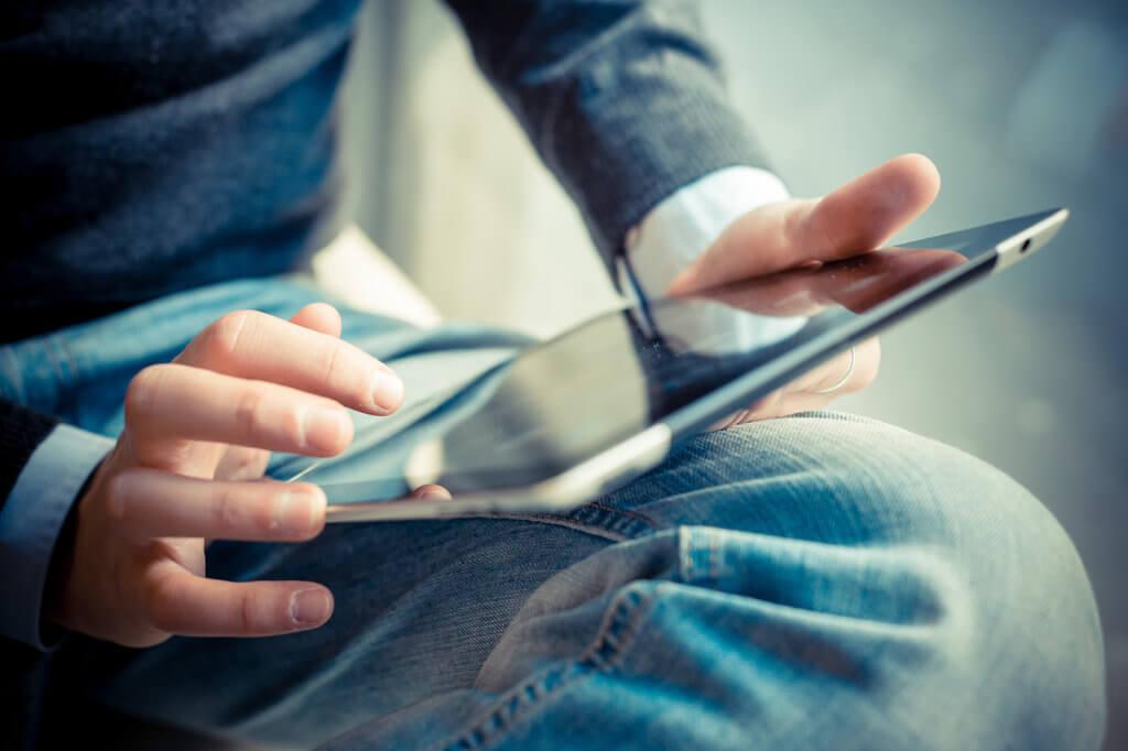 Mann arbeitet mit  Tablet auf dem Schoss