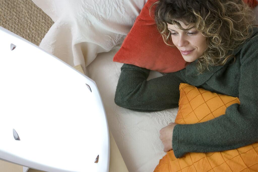 Frau liegt im Bett mit Tageslichtlampe