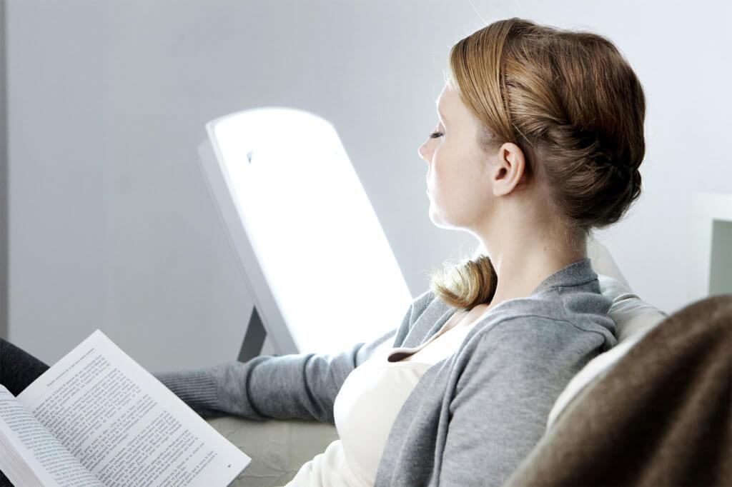 Frau liest ein Buch mit Tageslichtlampe