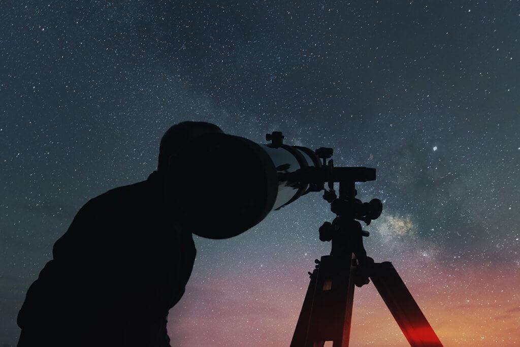Mann betrachtet Sternenhimmel mit Teleskop