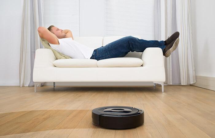 Mann entspannt auf Sofa und Wischroboter wischt